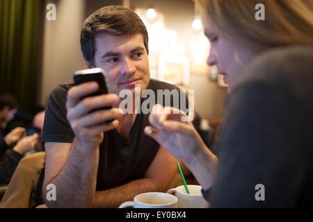 L'homme à l'aide de téléphone mobile pendant une réunion avec girl in cafe Banque D'Images