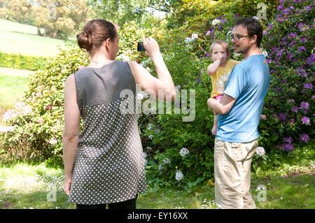 Maman de prendre une photo sur son portable de sa partenaire et petite fille à l'extérieur dans le jardin Banque D'Images