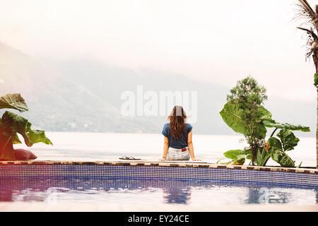 Jeune femme assise sur le bord de piscine, San Pedro, Lac Atitlan, Guatemala Banque D'Images