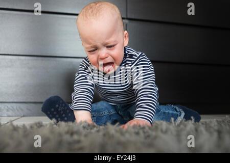 Bébé qui pleure garçon assis sur un tapis dans la salle de séjour Banque D'Images