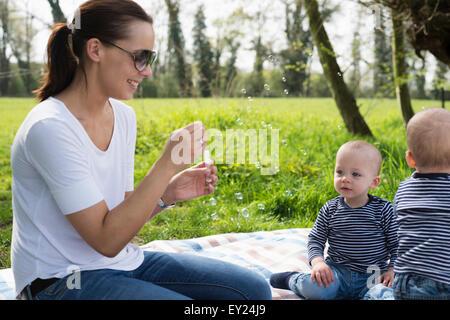 Jeune mère faire des bulles pour bébé jumeaux on picnic blanket Banque D'Images