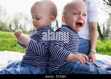 Les frères jumeaux bébé dos à dos sur la couverture de pique-nique dans le champ Banque D'Images