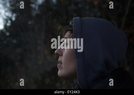 Close up portrait of mid adult woman gazing de forêt au crépuscule Banque D'Images
