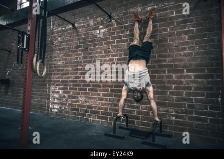 Young man doing handstand in gym Banque D'Images
