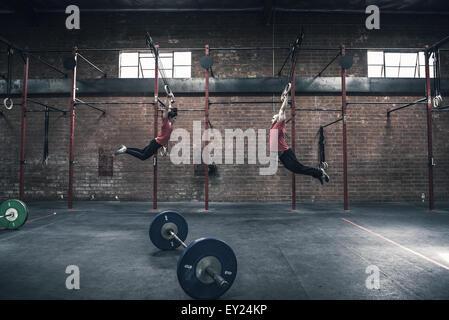 Jeune homme et femme se balançant sur les anneaux de gymnastique en salle de sport Banque D'Images