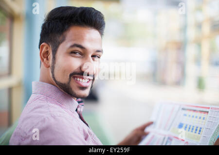 Young businessman reading newspaper in gare Banque D'Images