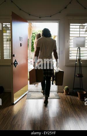 Vue arrière du jeune couple transportant des valises hors de porte avant Banque D'Images