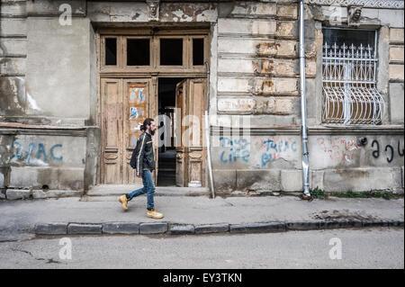 Un jeune homme barbu en passant devant une porte en bois ouverte sur une propriété délabrée à Tbilissi (Géorgie), Banque D'Images