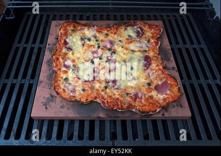 Des pizzas Speziale, tomates, jambon cuit, de salami et de fromage sur une pierre chaude dans un gril à gaz Banque D'Images