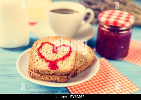 Jam formant un coeur sur un pain grillé, sur une table rustique en bois bleu, avec un effet inter-processus Banque D'Images