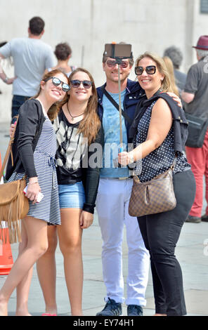 Londres, Angleterre, Royaume-Uni. Famille à Trafalgar Square en prenant une photo avec un bâton selfies Banque D'Images