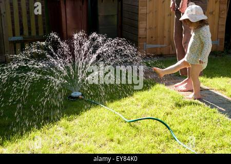 Petite fille se sentir l'eau à partir d'un arroseur de jardin son pied Banque D'Images