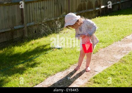 Petite fille en regardant ses pieds mouillés d'un sprinkleur jardin Banque D'Images