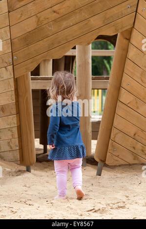 Vue arrière d'une petite fille qui marche vers une structure en bois Banque D'Images