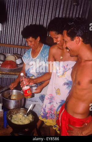 Frère, sœur et mère la cuisson et la préparation des aliments dans la cuisine typique à la maison sur l'île de La Banque D'Images