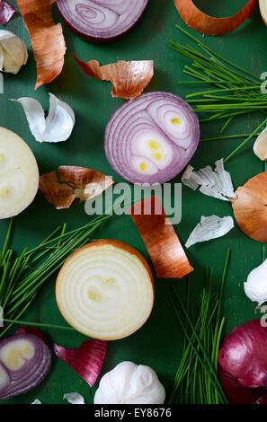 Les oignons, la ciboulette et l'ail éparpillés sur la vieille table de bois vert pour la préparation et la cuisson Banque D'Images