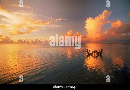 Couple sitting at table verre au coucher du soleil partage lagoon en milieu de l'océan Pacifique. Maison de vacances Banque D'Images