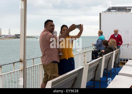 Les jeunes à couple d'âge moyen sur ferry boat holding baby à l'aide d'un iphone pour prendre une photographie selfies Banque D'Images