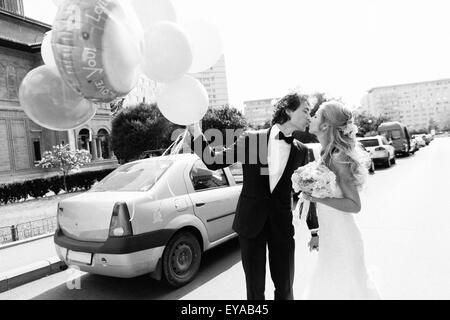 Les jeunes mariés couple kissing on a street. Image en noir et blanc avec film grain ajouté comme effet. Banque D'Images