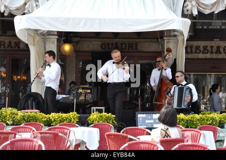 Piazza San Marco - Venise - Italie - cafe - scène orchestre jouer solitaire - jeunes femmes à une table - chaises Banque D'Images