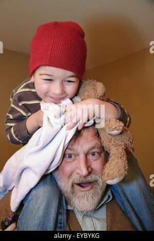 Trois ans à cheval sur les épaules de son grand-père, serrant son ours en peluche et une couverture, à Issaquah, Washington, USA