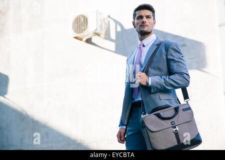 Portrait d'un confident businessman standing en plein air près de l'immeuble de bureaux Banque D'Images