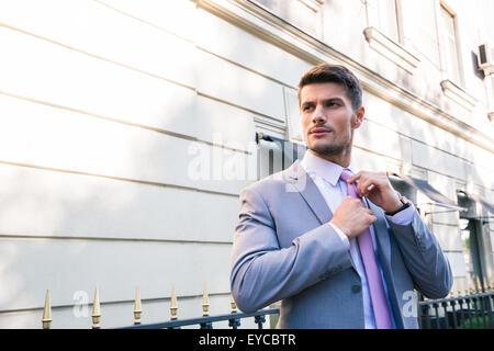 Handsome businessman redresse sa cravate en plein air Banque D'Images