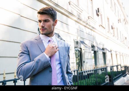 Confident businessman redresse sa cravate en plein air Banque D'Images