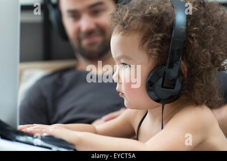 Close up of young woman typing on laptop alors que père watches Banque D'Images