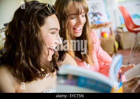 Deux jeunes amies et riant de livres navigation Banque D'Images