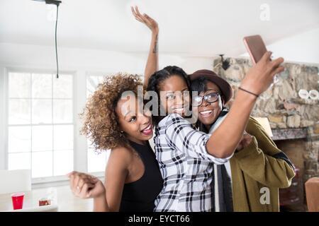 Trois jeunes femmes se faisant passer pour smartphone cuisine en selfies Banque D'Images