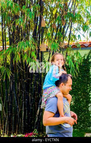 Portrait de fille obtenant une épaule effectuer de père en jardin Banque D'Images