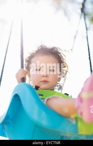 Jeune fille sur jeux pour enfants balançoire, low angle view Banque D'Images