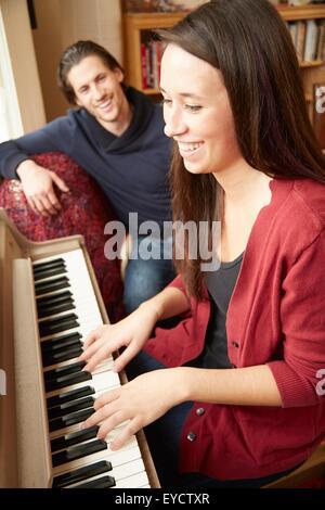 Jeune femme jouant du piano pour petit ami Banque D'Images