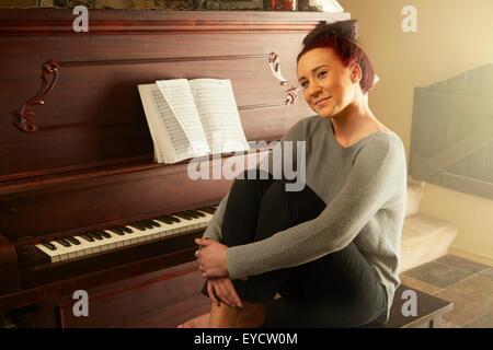 Portrait de jeune femme assise sur le tabouret de piano serrant les genoux Banque D'Images