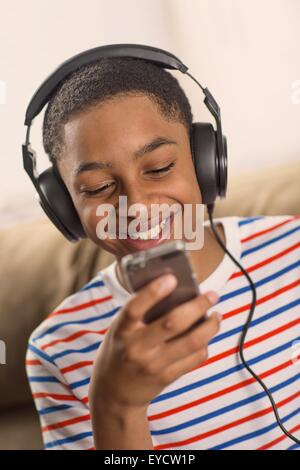 Teenage boy wearing headphones lecture textes smartphone Banque D'Images