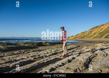 Jeune homme debout sur la plage à la recherche de l'ocean