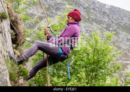 Female rock climber abseiling avec une corde et harnais d'escalade sur un rocher. Ogwen, Snowdonia, le Nord du Pays Banque D'Images