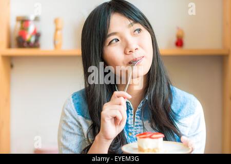 Portrait of young asian pretty smiling woman eating cake au café, belle femme tenir strawberry cake Banque D'Images