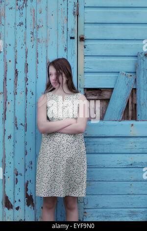 Une fille dans une robe florale est debout devant un mur en bois bleu Banque D'Images