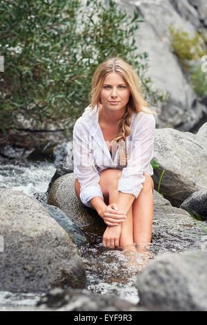 Jeune femme blonde assise sur un rocher avec ses pieds dans un ruisseau de montagne après une randonnée. Banque D'Images