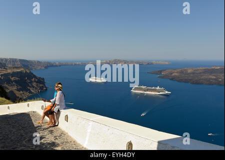 Un jeune couple de prendre une photo d'eux Selfies avec deux navires de croisière dans la distance, Santorini, Grèce.