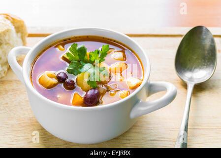 Bol de soupe minestrone garnie avec du persil frais et avec la baguette et cuillère en argent de côté libre Banque D'Images