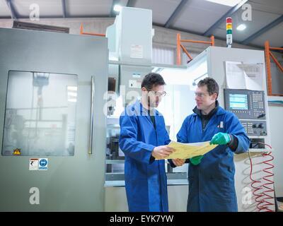Les travailleurs dans la discussion à côté de machine CNC en usine de matières plastiques, portrait Banque D'Images