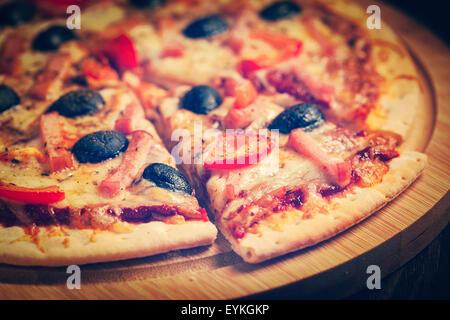 Effet Retro Vintage style hipster filtrée image de jambon en pizza avec poivrons et olives sur planche de bois sur Banque D'Images