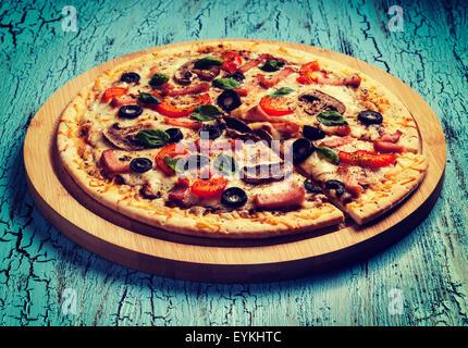 Effet Retro Vintage style hipster filtrée image de pizza jambon avec capsicum, champignons, les olives et les feuilles Banque D'Images