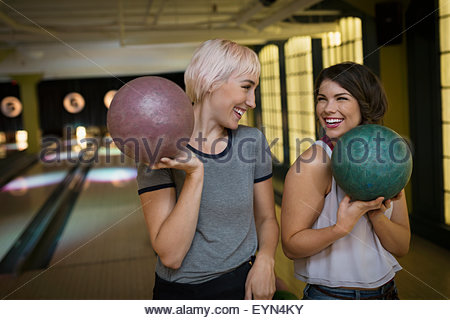 Smiling young women holding bowling balls Banque D'Images
