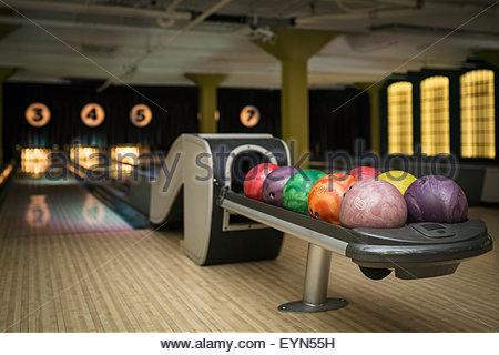 Boules multicolores sur rack au bowling Banque D'Images