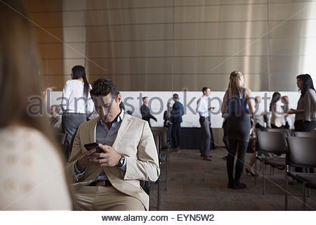Man using cell phone in auditorium public Banque D'Images