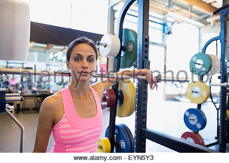 Portrait femme confiante à barbell in gym Banque D'Images